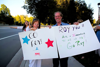 Wiegand's parents, Bridget and Roy (a trombone player), await their son at the finish line proudly holding signs of encouragement and congratulations.